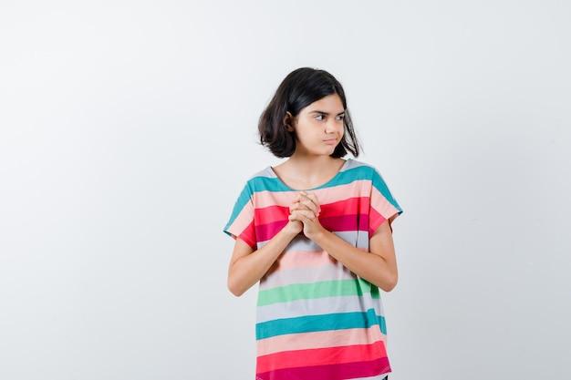 手を握りしめ、カラフルなストライプのtシャツで目をそらし、きれいに見える若い女の子。正面図。