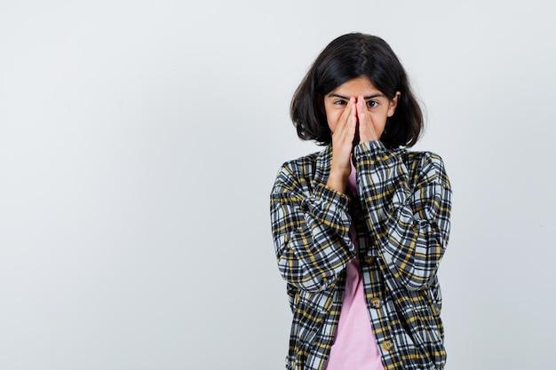 Молодая девушка, сложив руки на лице в клетчатой рубашке и розовой футболке, выглядела взволнованной. передний план.