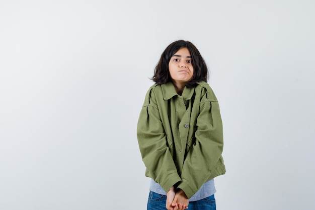 Young girl clasping hands, posing  in grey sweater, khaki jacket, jean pant and looking cute , front view.