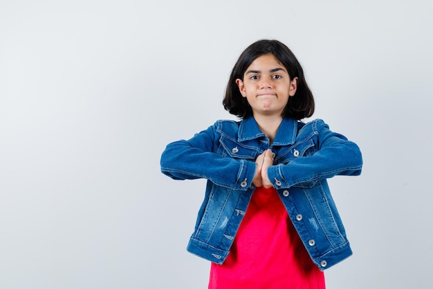 Young girl clasping hands in prayer position in red t-shirt and jean jacket and looking calm. front view.