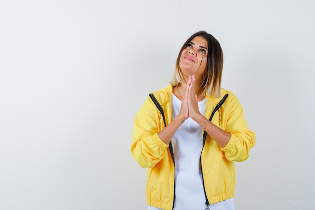 Young girl clasping hands in praying position in white t-shirt , yellow jacket and looking cheery , front view.