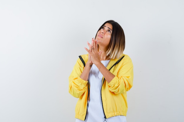 Young girl clasping hands in praying position in white t-shirt , yellow jacket and looking focused , front view.