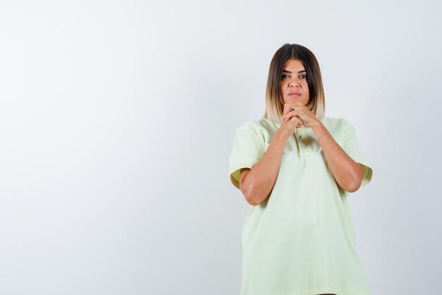 Tシャツのあごの下で手を握りしめ、真剣に見える少女。正面図。