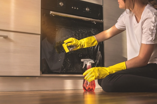 나무 바닥에 스프레이 병 세제로 주방 오븐을 청소하는 어린 소녀