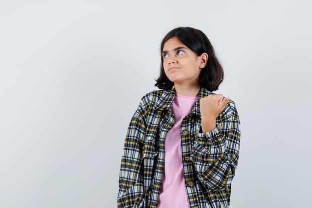 拳を握りしめ、チェックシャツとピンクのtシャツで目をそらし、物思いにふける、正面図を見て若い女の子。