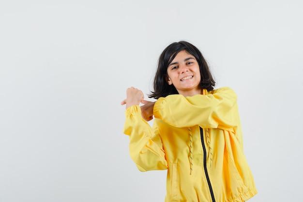 어린 소녀 주먹 떨림과 노란색 폭격기 재킷에 왼쪽을 가리키는 행복 찾고.