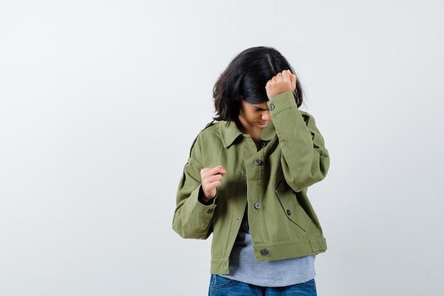 若い女の子は拳を握りしめ、灰色のセーター、カーキ色のジャケット、ジーンズのパンツで頭に手を置き、疲れているように見えます。正面図。
