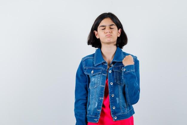 拳を握りしめ、赤いtシャツとジージャンで目を閉じ、落ち着いて見える少女、正面図。