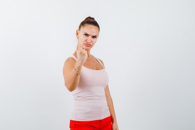 ベージュのトップと赤いズボンで拳を握りしめ、自信を持って見える少女。正面図。