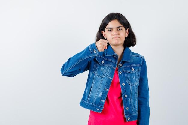 赤いtシャツとジージャンで拳を握りしめ、真剣に見える少女。正面図。