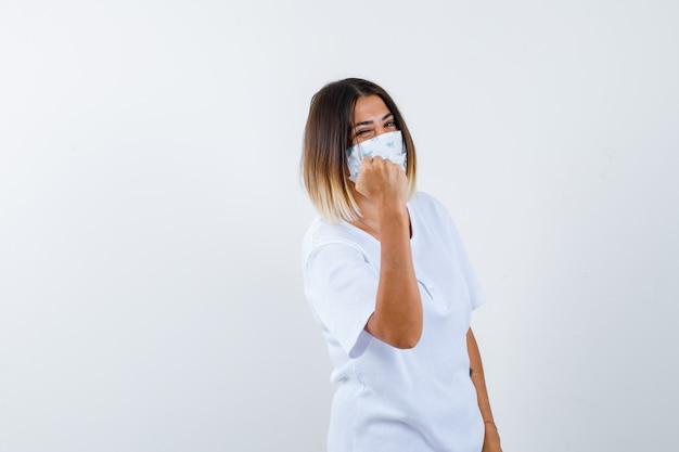 어린 소녀 흰색 t- 셔츠와 마스크에 주먹을 떨림과 자신감, 전면보기를 찾고.