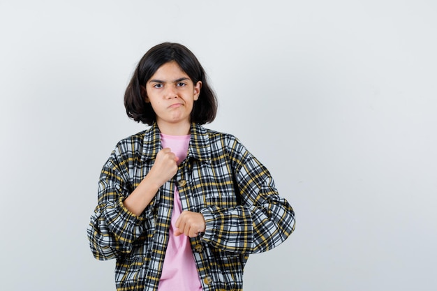 Young girl clenching fists in checked shirt and pink t-shirt and looking angry.