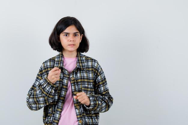 チェックシャツとピンクのtシャツで拳を握りしめ、怒っているように見える少女、正面図。