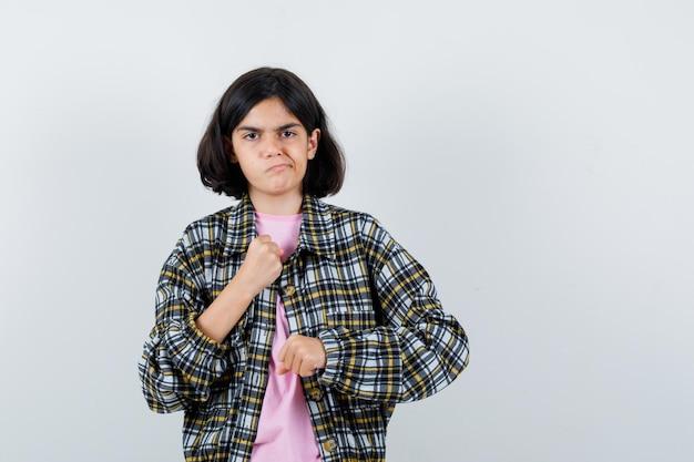 チェックシャツとピンクのtシャツで拳を握りしめ、怒っているように見える少女。
