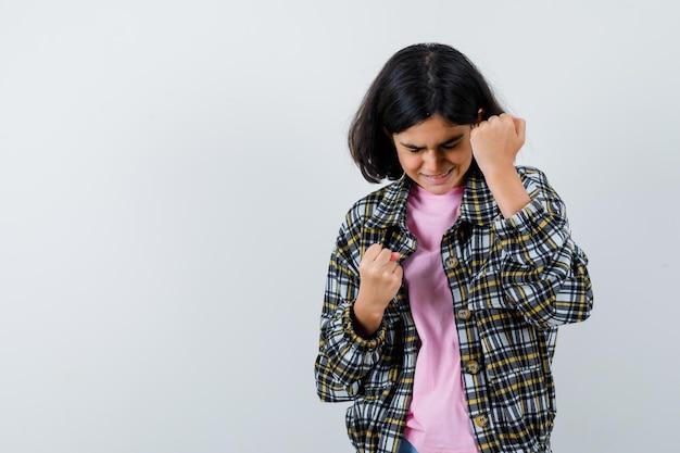 チェックシャツとピンクのtシャツで拳を握りしめ、イライラして見える少女。正面図。
