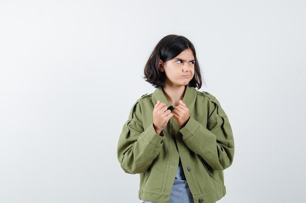 拳を握りしめ、灰色のセーター、カーキ色のジャケット、ジーンズのパンツで目をそらし、かわいい、正面図を見て若い女の子。