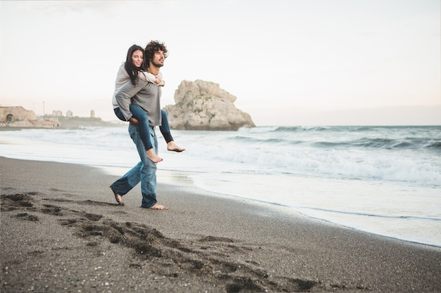 Young girl climbing on a man's back on the beach
