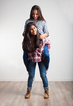 別の女の子の背中に登る若い女の子