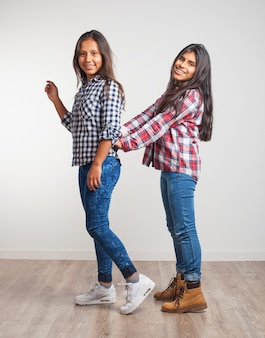 Young girl clinging to another girl's hip