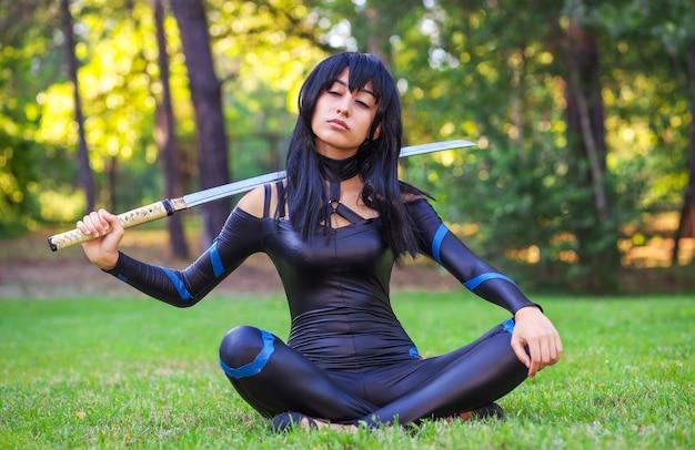 Молодая девушка с закрытыми глазами сидит на траве и держит самурайский меч. оригинальный косплей персонажа