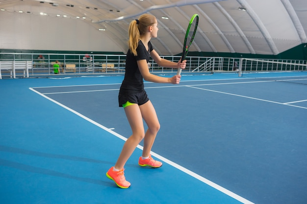 Young girl in a closed tennis court with ball