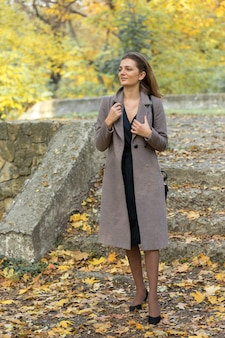 A young girl in a coat poses in a park on a background of golden autumn foliage.