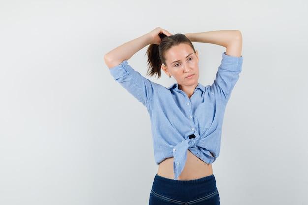 青いシャツ、ズボンで髪を集めて物思いにふける少女。