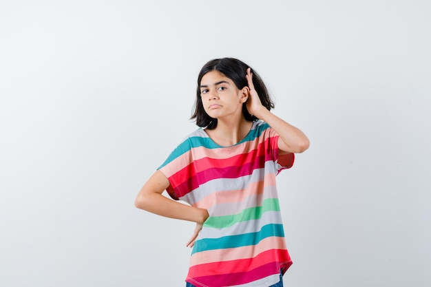 Young girl in colorful striped t-shirt holding one hand on waist, another hand near ear to hear something and looking focused , front view.