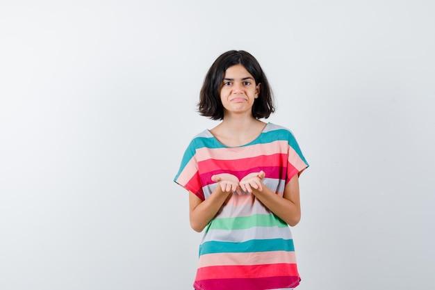 Giovane ragazza in t-shirt a righe colorate che invita a venire e sembra felice, vista frontale.