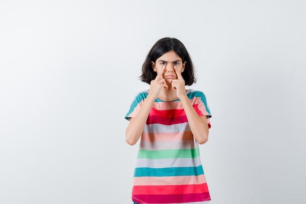 Giovane ragazza in maglietta a righe colorate che tira giù le palpebre e sembra seria, vista frontale.