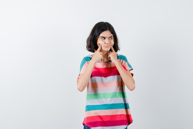 Young girl in colorful striped t-shirt putting index fingers near mouth, forcing a smile and looking happy , front view.