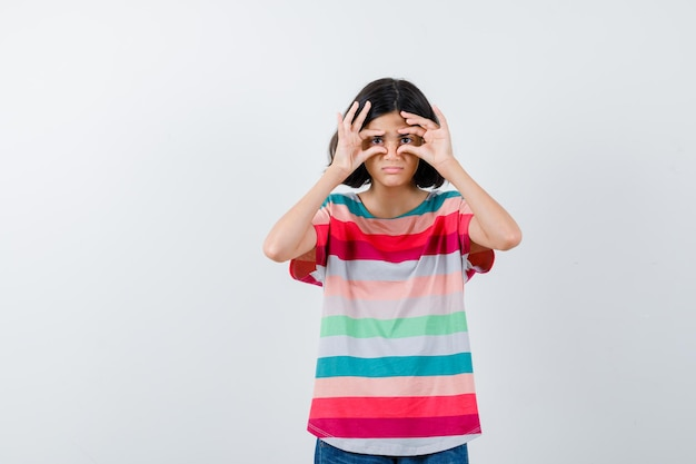Giovane ragazza in maglietta a righe colorata che mostra il gesto del binocolo e sembra carina, vista frontale. Foto Gratuite