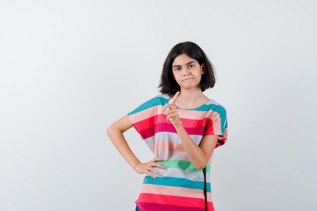 Giovane ragazza in maglietta a righe colorate che mostra gesto di avvertimento mentre tiene la mano sulla vita e sembra seria, vista frontale.
