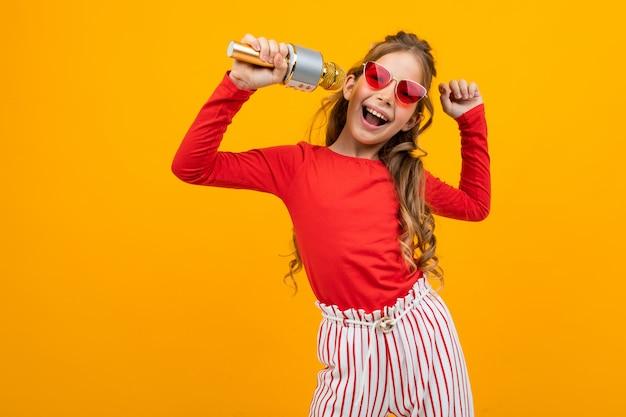 Молодая девушка отрывается на музыку с микрофоном в руках на желтом с копией пространства