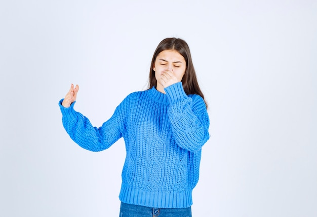 Young girl coning her nose because of smell on white.