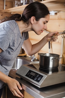 A young girl cooks soup on an electric stove and tastes
