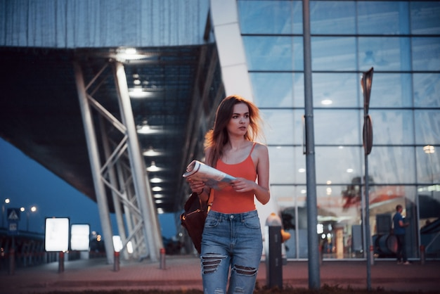 若い女の子は、空港または駅のターミナルの近くで、市内地図を読んだり、ホテルを探したりして、夜にかかります。バックパックを持つかわいい観光客が旅行の概念を決定します