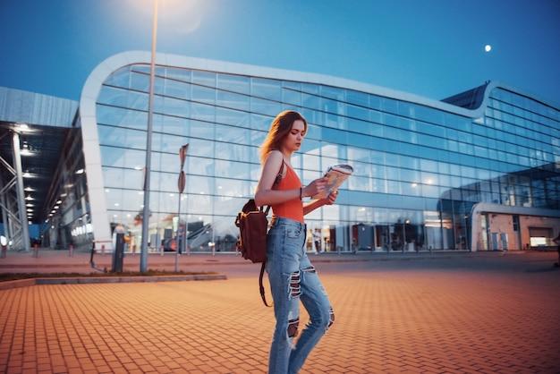 Молодая девушка стоит ночью возле терминала аэропорта или вокзала и читает карту города и ищет отель. милый турист с рюкзаками определяет концепцию путешествия