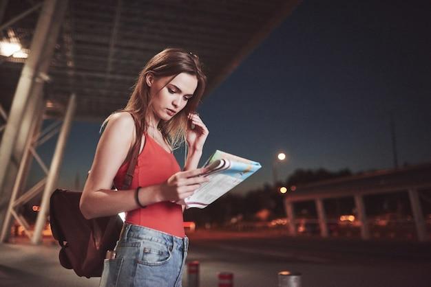 어린 소녀는 공항이나 역의 터미널 근처에서 밤에 비용을 지불하고 도시지도를 읽고 호텔을 찾습니다. 배낭이 달린 귀여운 관광객은 여행의 개념을 결정합니다.