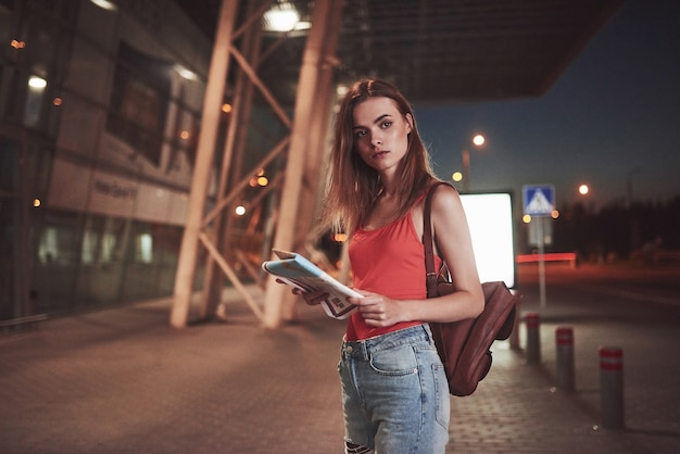Young girl costs at night near the terminal of the airport or station and reading city map and looking for hotel. cute tourist with backpacks determine the concept of travel.