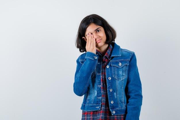 체크 셔츠와 진 재킷에 손으로 눈을 덮고 심각한 찾고 어린 소녀.