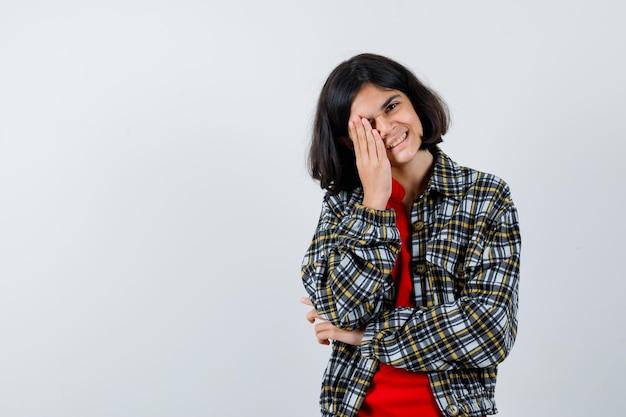 Giovane ragazza che copre l'occhio con la mano, ride in camicia a quadri e maglietta rossa e sembra felice, vista frontale.