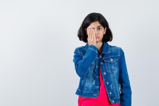 Giovane ragazza che copre l'occhio con la mano in maglietta rossa e giacca di jeans e sembra carina, vista frontale.