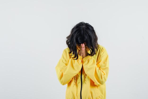 노란색 폭격기 재킷에 한 손으로 눈을 덮고 심각한 찾고 어린 소녀.
