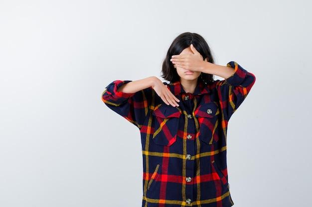 チェックのシャツで別の手を伸ばして真剣に見ながら手で目を覆っている少女。正面図。