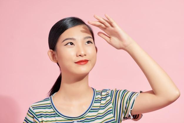 Молодая девушка закрывает лицо рукой от солнечного света