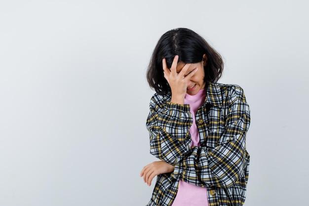 Молодая девушка закрыла лицо рукой в клетчатой рубашке и розовой футболке и выглядела взволнованной, вид спереди.