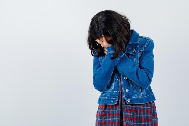 Молодая девушка закрыла лицо руками в клетчатой рубашке и джинсовой куртке и выглядела взволнованной. передний план.