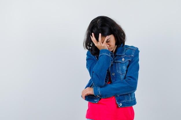 빨간 티셔츠와 진 재킷으로 이마를 덮고 피곤해 보이는 어린 소녀.