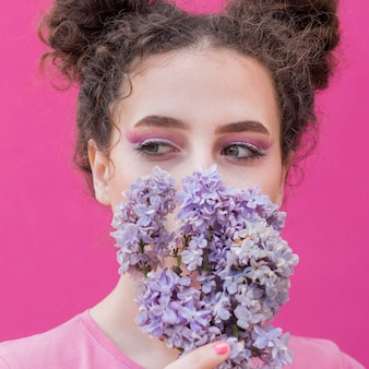 Young girl covering her face with lilac flowers